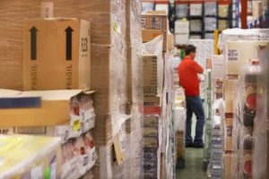 Man in the warehouse taking stock of his inventory, which is funded with a business loan