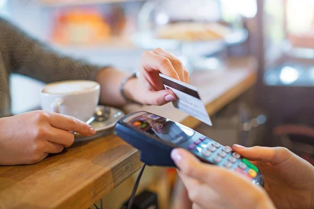Man making card payment to a credit card processor wired up on merchant cash advance plan