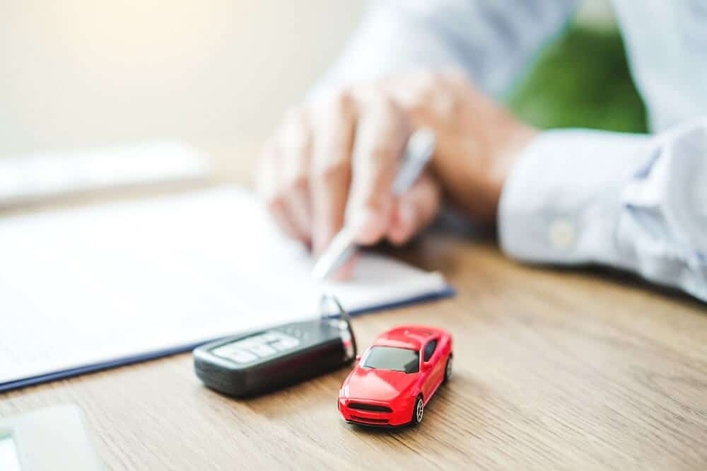 Car keys and a red toy car on a table, with man signing a car financing business loan in the background