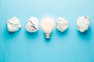 Light bulb in the middle of crumpled paper balls showing that an idea is what you need to start a business in Singapore