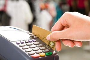 Woman swiping a credit card on a payment machine that's hooked up to a merchant cash advance plan