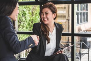 A business owner shaking hands with an SME loan broker