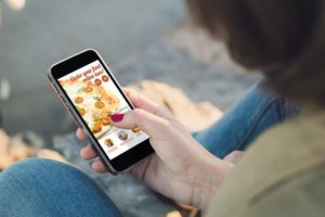 Woman ordering food on a mobile app launched by a company using business loans